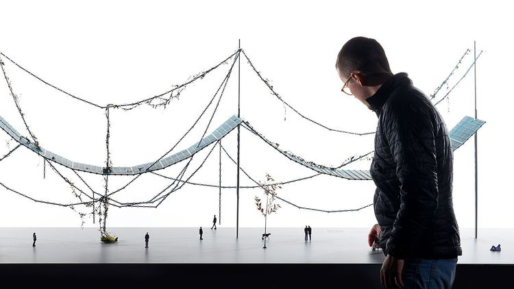 Man standing in front of architectural diorama with miniature people.