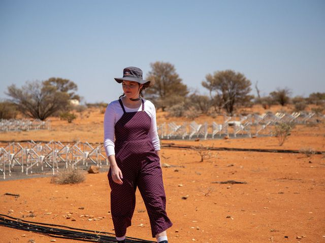 Female walking on red soil with hat on.