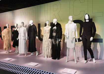 Plinth with 4 female mannequins and 2 male mannequins wearing a mixture of casual and formal clothing.