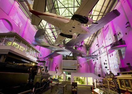 Transport Exhibition Gallery including aeroplanes hanging from the ceiling and fuschia lights colouring the walls