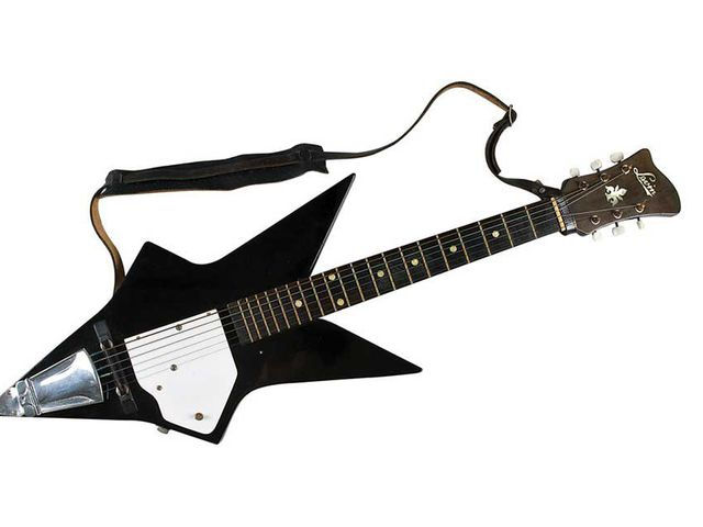 Electric guitar, solid body is mostly black with a white scratchplate. The shape of the body is that of a five-pointed star. Metal bridge screwed to the body. Wooden saddle. One pick-up. The headstock has the word 'Levin' and a floral symbol inlaid [in mother-of-pearl]. Machine heads have white tuning pegs. A dark brown leather strap is attached to the guitar.