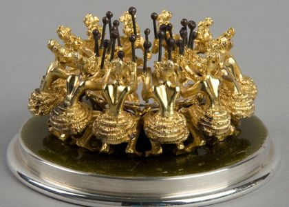 Small model of 12 figures drumming in a circle. Made of silver and gold