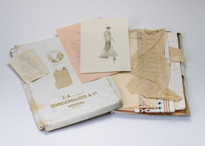Contents of dressmaking kit, including box, fabric, embroidered inserts, fashion illustration, contents list and washing instructions.