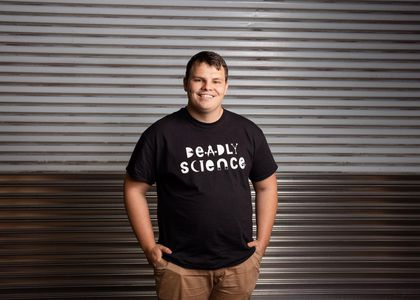 Man in black tshirt with the words 'deadly science' standing in front of iron gate