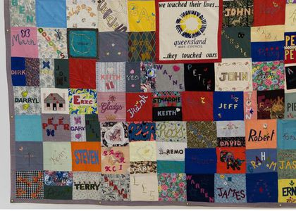 Multi coloured patchwork quilt with a different male's name per square