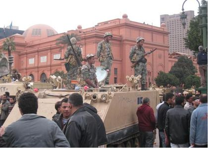 Soldiers standing on top of a tank in a crowded public space