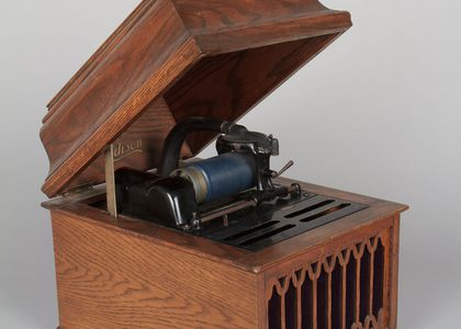 Phonograph with wooden display box, which has an internal metal horn and fixed playing mechanism on the centre top. The wooden display box has a hinged lid which can be propped open.