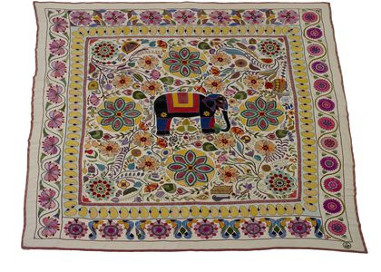 A large, square, hand embroidered quilt on a cream background. The outside edge has been bound with red stitching in a zig-zag pattern. The dominant central motif is a black elephant embroidered with trappings and flowers, surrounded by four padma (lotus), amidst a profusion of gaily coloured plants, birds and symbols of everyday life. The central panel is surrounded by dark red herringbone stitching. The outer border consists of red and pink flowers and green leaves which are varying interpretations of the lotus flower, being different on each of the four sides. On each of the long sides the lotus are interspersed with a sweeping 's' line. Inside that border again, on a pale blue background, there is a row of yellow boteh (in Bangladesh, kalka) motifs.