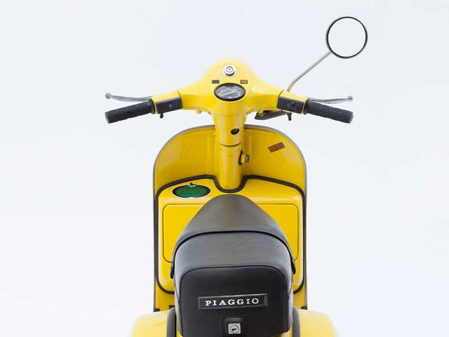 Vespa motor scooter consisting of yellow step-through frame, front leg shield, handlebars, mudguards, and floorboard with black tread. The motor is a 200cc, 2 stroke, situated under the lift up black upholstered seat. Kickstand situated to the side of the floorboard. Key ignition on the right-hand side of the steering shaft.