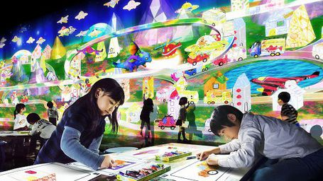 Children colouring-in in front of a colourful light projection of a busy town.