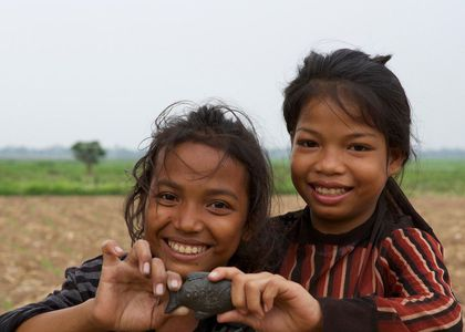 Two smiling children holding a Lucky Iron Fish cooking tool