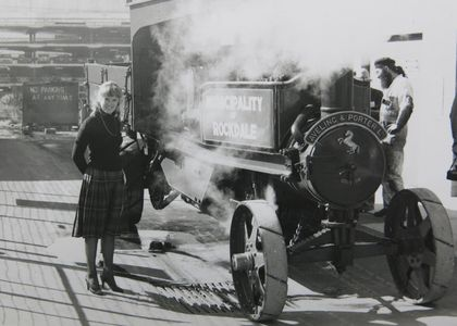 A young woman wearing a kilt is looking at the photographer and stands next to a steam wagon. The steam wagon, which is surrounded by clouds of steam, is standing on a concrete pavement outside a workshop. A steam wagon is a self-propelled steam-powered truck with a timber tip tray. The side of the steam wagon has the wording 'Municipality of Rockdale' for whom the wagon was built and the front has the manufacturer's name, 'Aveling & Porter'. A man with a long beard is standing on the other side of the wagon looking at the wagon's steam engine.