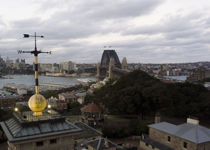 Aerial photo with a weathervane, mounted on top of a large yellow time ball, with various sandstone buildings below. The Sydney Harbour Bridge, The Rocks area, Sydney Harbour and Luna Park can be seen in the background.