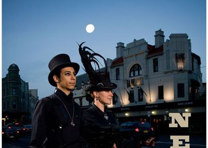 A man and women in Gothic attire on King Street, Newtown with the Bank Hotel in the in the background. Text in image