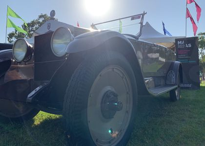 Low angle close shot of a dark and light brown classic car on grass. Front left wheel is the closest object in the photo. The sun is at the centre of the top section of the photo.