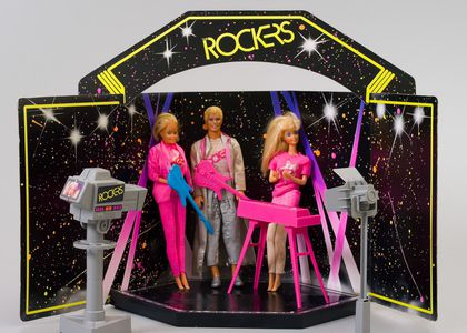 The two Barbie dolls' costumes consist of a pink 'Rockers' T-shirt, one doll has a pink mini-skirt and tan leggings; the other has a pink jacket and pants ensemble. The styling is indicative of the mid 1980s. The Ken doll's costume is a silver long jacket and pants ensemble with a silver 'Rockers' T-shirt, and silver shoes.