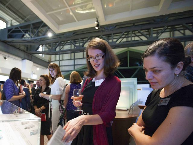 Women pointing at contents of a museum display while others walk through Engineering Excellence Awards exhibition around them