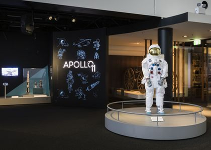 A mannequin wearing a space suit stands on a silver circular plinth. To the left is a title wall reading 'Apollo 11' with diagrams of spacecraft around it.