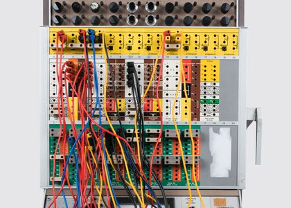 Front view of Pace TR20 analogue computer. Two rows of knobs run across the top of the machine and wires are plugged into the removable patch panel below. At the machines base on a slanted panel is a set of dials and indicators.