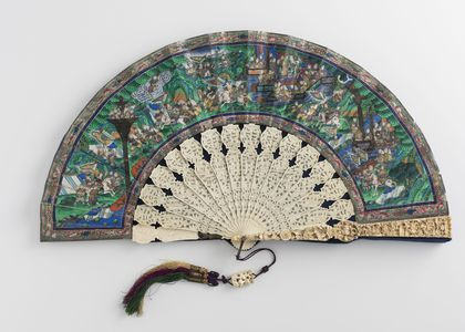 Chinese folding fan open on a grey background. The blades are intricately carved ivory and the painted paper surface (leaves) portrays a busy landscape, depicting what looks like a historic scene with many small brightly coloured figures.]