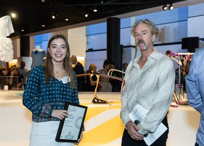 A young woman holding a certificate and a grey-haired man pose in front of an exhibition space.