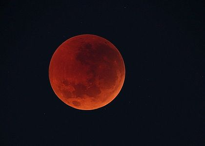 Red umber moon in the night sky