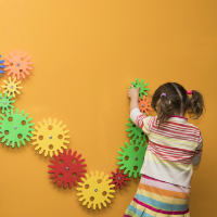 Photograph of a young girl playing with cogs in the Experimentations exhibition. Click to view events at Powerhouse Museum.