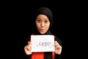 Delina Darusman-Gala holding a sign with upside-down text saying 'Quirky!'