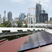 Solar cells on a red roof are in the foreground. The Sydney skyline is in the background.