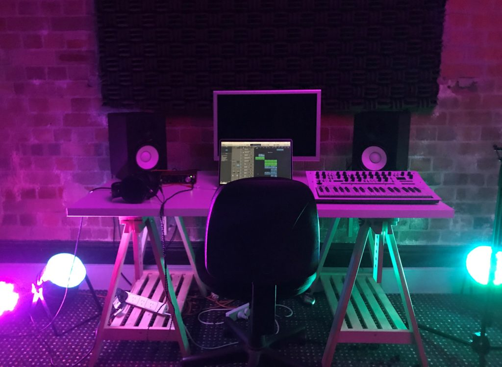 Detail of studio set-up including, a table, chairs, laptop and speakers with purple lighting.