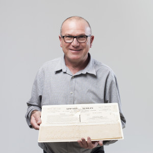 Matthew Connell, Principal Curator, with piece of paper punched to be used in a Jacquard weaving machine and found in a box with the letters of Charles Babbage.