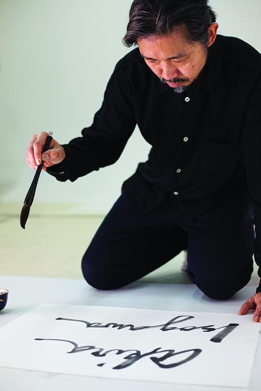Akira Isogawa signing his name in calligraphy