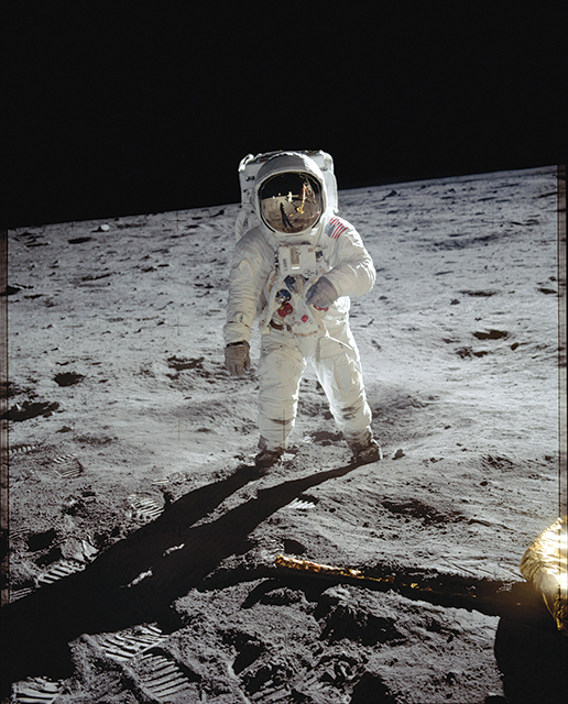 Man in spacesuit walking across rocky terrain of moon