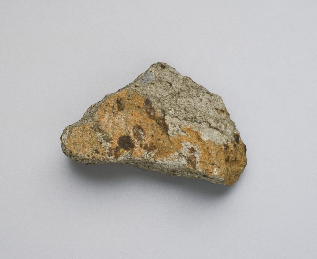 A photograph of a brown and grey stone against a grey background.