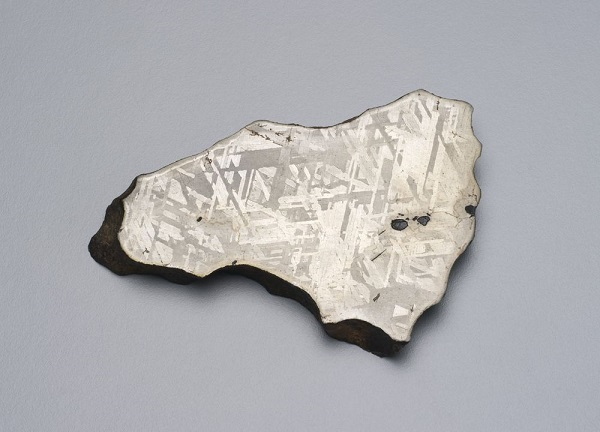 A photography of a cross-section of a silver rock against a grey background.