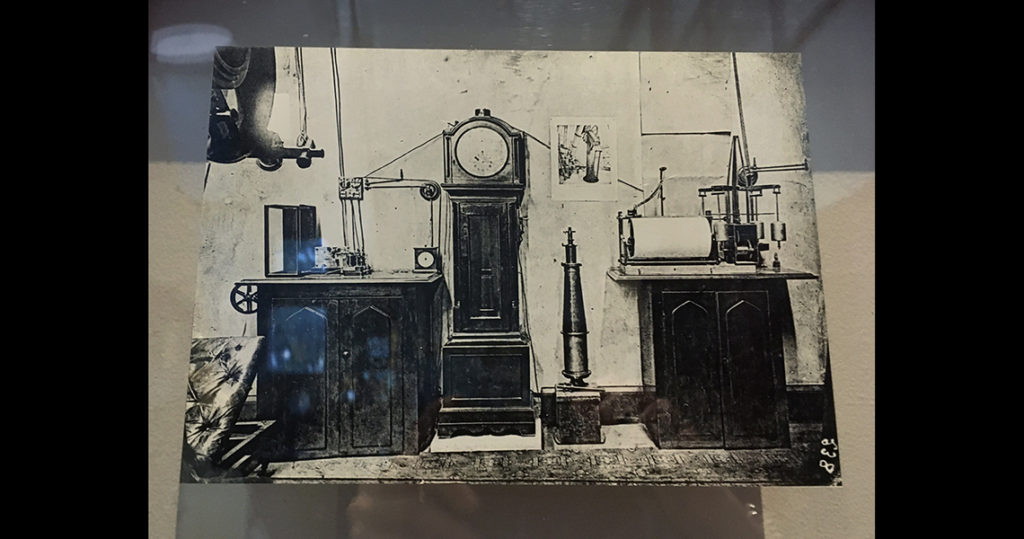 Black and white image of historical clocks and instruments