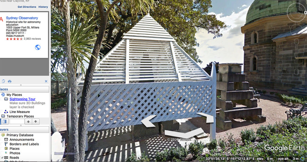 A white, shuttered pyramid structure on a lawn