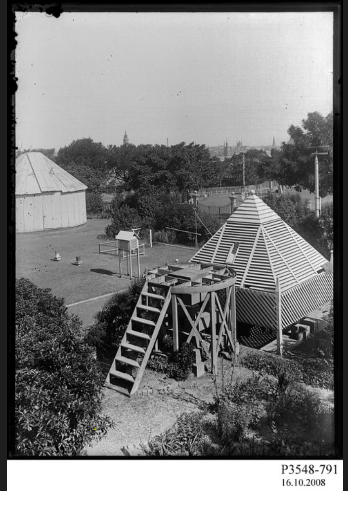 Black and white photo of a lawn with a stone pyramid structure and a shuttered pyramid structure behind it