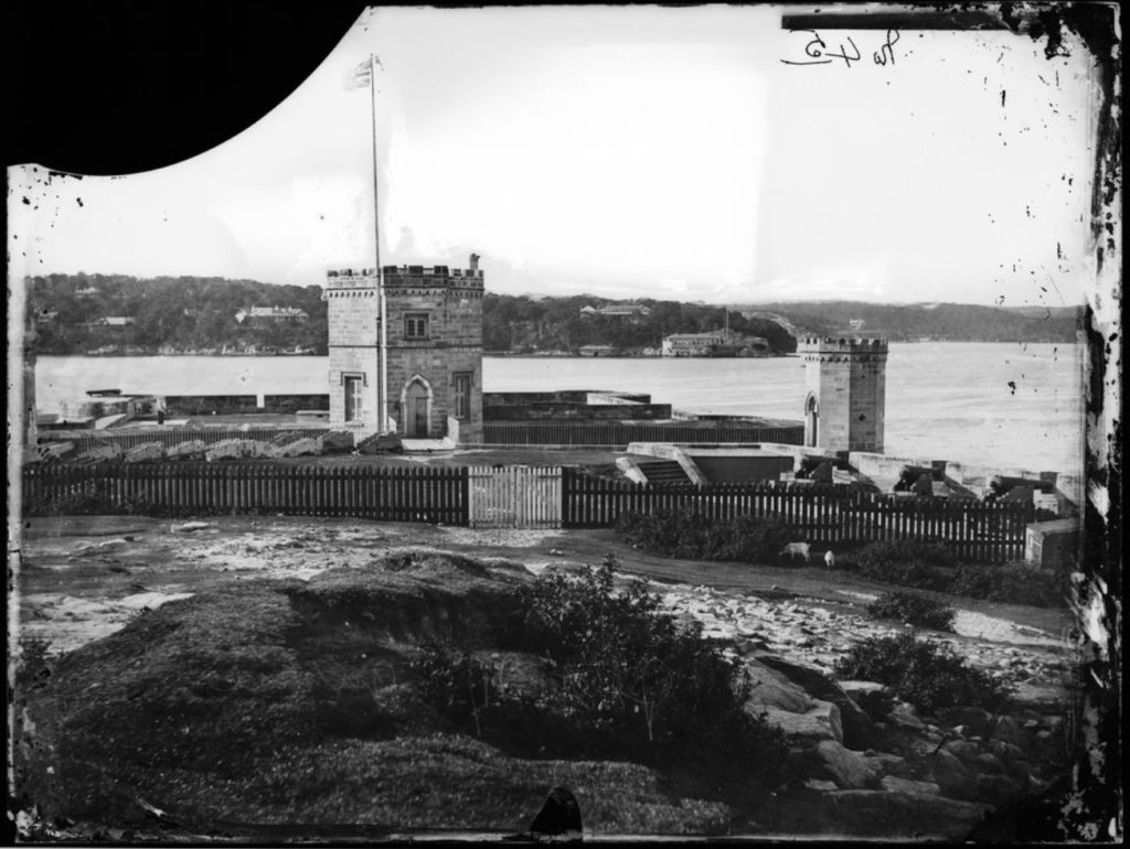 Black and white image of a historic fort on a rocky coast.