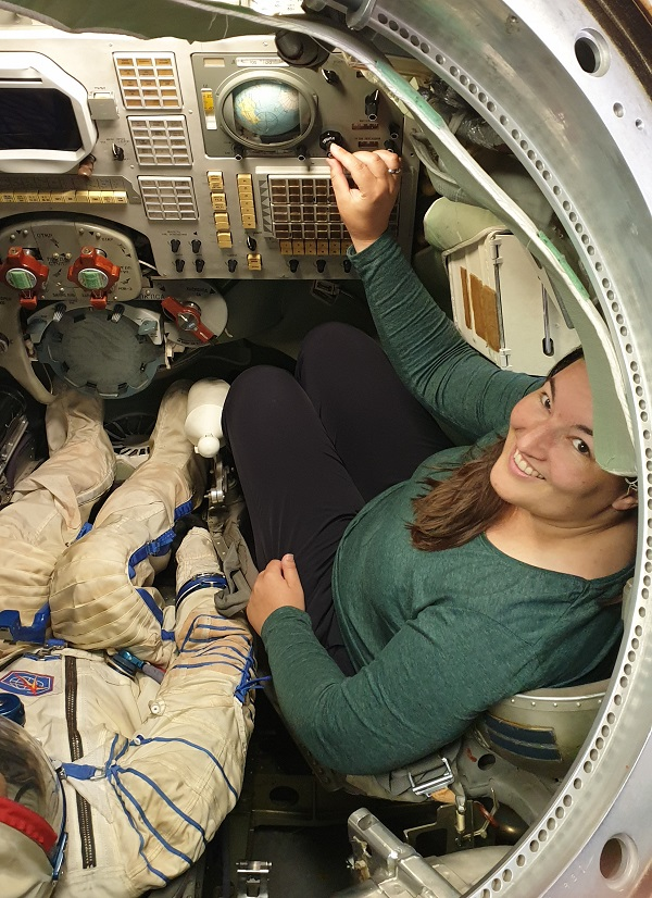 A woman smiles from a steel capsule beside a figure in an astronaut suit