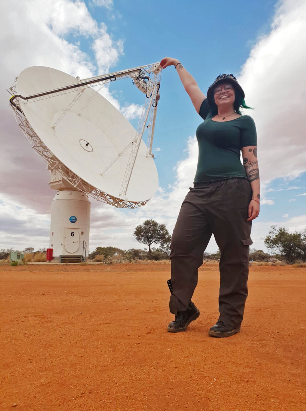 A woman stands infront of a large radio telescope in a desert landscape