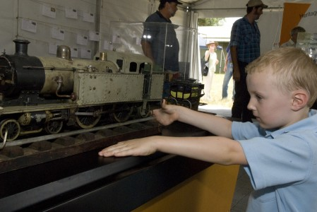 Boy looking at model steam engine