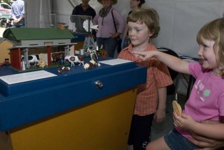 Children looking at die-cast farm animal toys