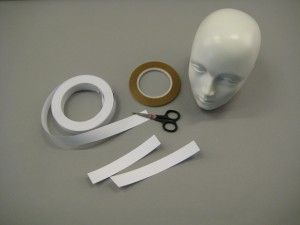 Mannequin head, scissors, paper tape and sticky tape.