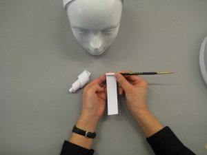 Paper stripes being rolled up to create curls