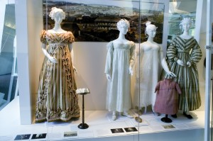 Display case with four mannequins with dresses and paper hairstyles