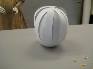 Stripes of paper being placed on top of mannequin head