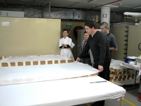 Assistant Collections Manager, Einar Docker demonstrates the single sheet of acid free tissue used to protect textiles