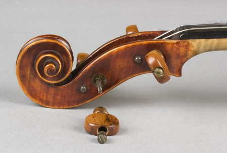 Scroll at the top of the viola, with one of the string pegs unscrewed, side view