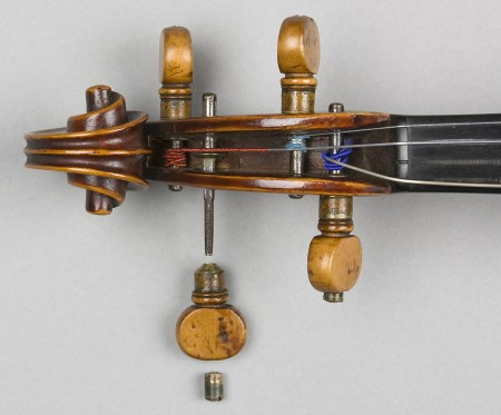 Scroll at the top of the viola, with one of the string pegs unscrewed, top view